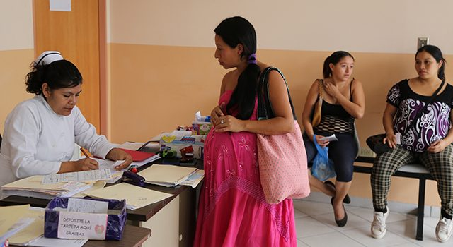 Image of a pregnant woman registering with a nurse sitting at a desk.
