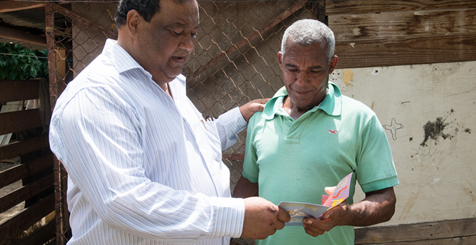 Photo of two men exchanging a card.